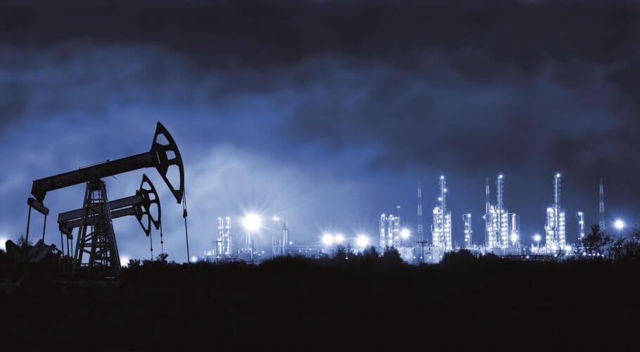 Pump jack and grangemouth refinery at night.